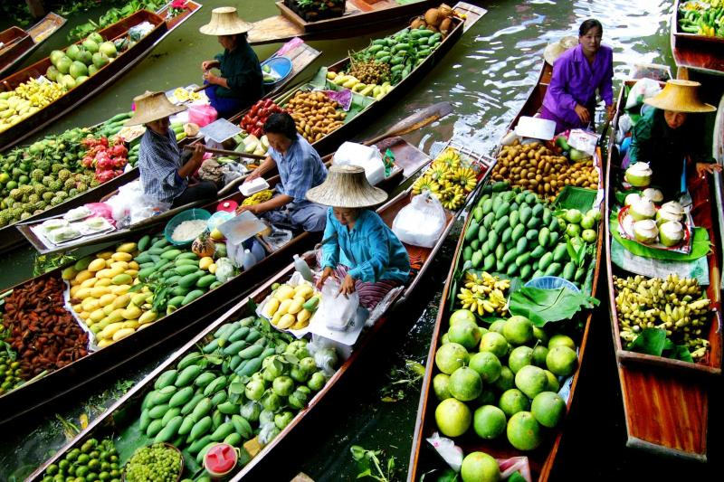 Locals selling fresh tropical fruits on boats